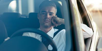 Man driving car looking worried