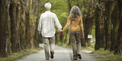 Couple walking down the street holding hands.