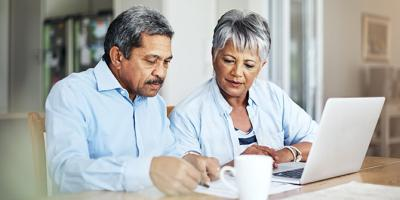 Senior couple using a laptop to review their retirement savings