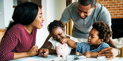 Mom and dad watch child add money to piggy bank