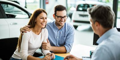 Man and woman talking with car salesman in a showroom