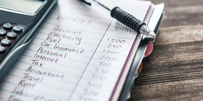 Handwritten budget in a notebook next to a calculator on a desk