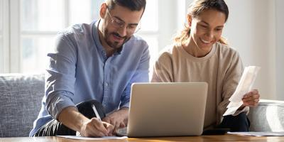 Man and woman using laptop and reviewing bills