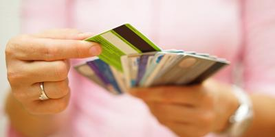 Female hand choosing between retail and credit cards