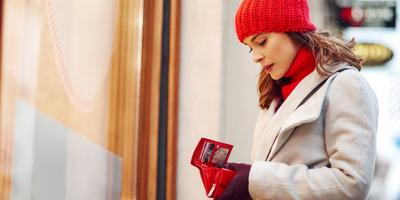 Woman standing outside store looking into wallet