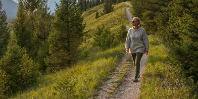 Older woman walking and looking out to mountain ranges in distance