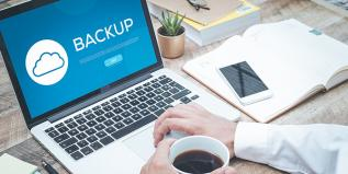 The word backup on a laptop screen with hand holding cup of coffee