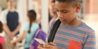 Young boy holding a smart phone and a backpack