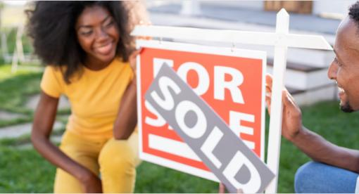 Couple kneeling next to a home sold sign.