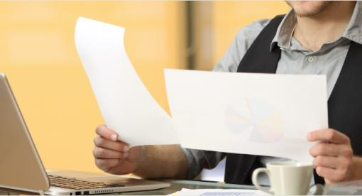 Man sitting a desk comparing two pieces of papers.